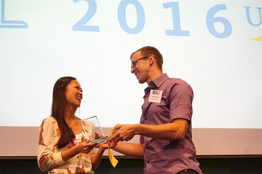 Last year's UCSB Grad Slam Champion, Danny Hieber, presents the 2016 award to Nicole Leung. Credit: Patricia Marroquin