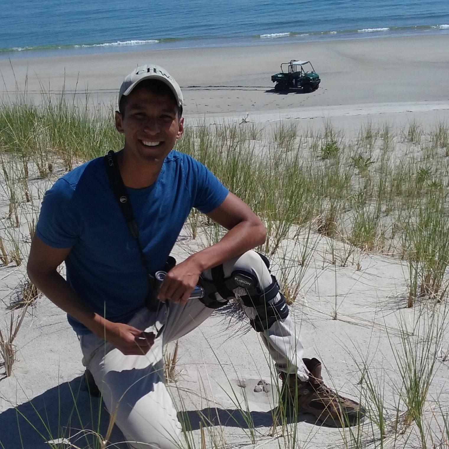 Erik next to a piping plover nest during field surveys at Crane Beach in Ipswich, MA. Photo courtesy of Erik Martinez