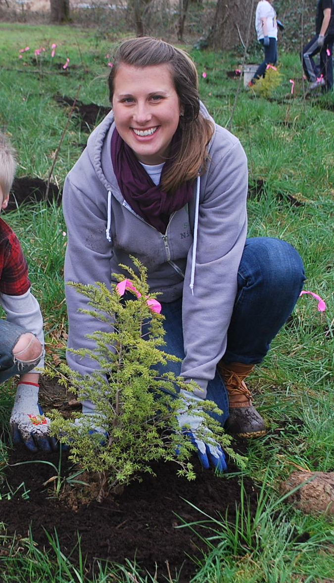 Nicole planting native trees and shrubs with local K-12 students in Portland, Oregon.